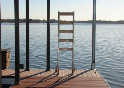 A five step metal ladder sitting on a wood topped deck with a lake and trees in the background