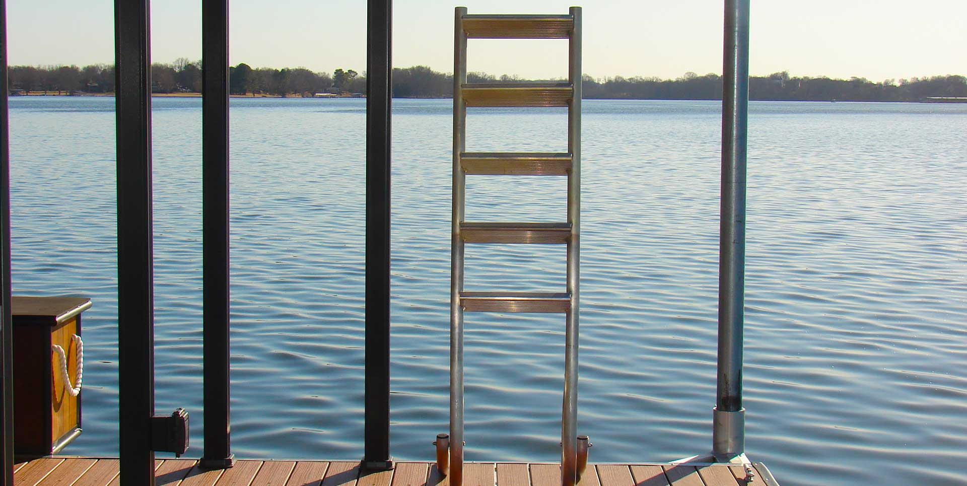Boat dock with ladder attached and river in the background