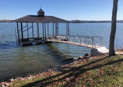 A gangway leading from a grassy shore to an aluminum wahoo boat dock with a dark pitched roof on a river