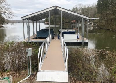 Looking down a gangway to an aluminum wahoo boat dock with a roof and two boat slips with boats in them