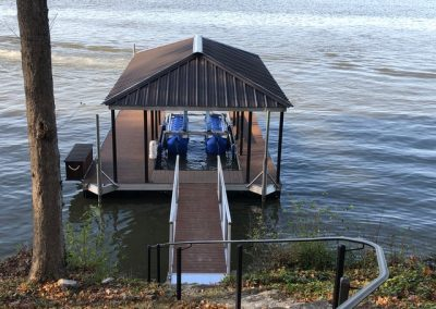 Looking down a hill to a gangway leading to an aluminum wahoo boat dock with a brown roof and a blue boat lift