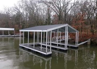 A white and grey aluminum wahoo boat dock with a roof and two boat slips on a river with a gangway leading to shore