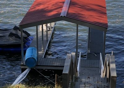 Looking down at the steps of wooden gangway to an aluminum wahoo boat dock with a red roof and two jet skis on lifts to the side