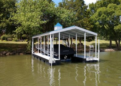 An aluminum wahoo boat dock with a white and blue roof and a white boat with a black cover on it docked and trees in the background