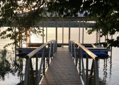 Looking down a gangway to an aluminum wahoo boat dock with a dark pitched roof and sunset in the background