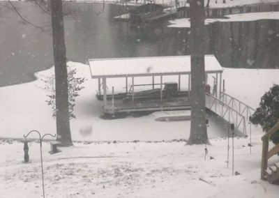 A snow covered hill leading down to a gangway and aluminum wahoo boat dock on a snow covered river