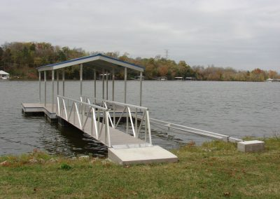A gangway leading from a grassy shore to an aluminum wahoo boat dock with a blue roof and trees in the background