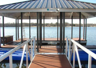 Looking down a gangway with two blue jetski lifts on either side of it to an aluminum wahoo boat dock with a dark pitched roof