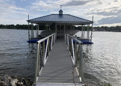 Looking down a gangway to an aluminum wahoo boat dock with a dark pitched roof and a white boat docked under it