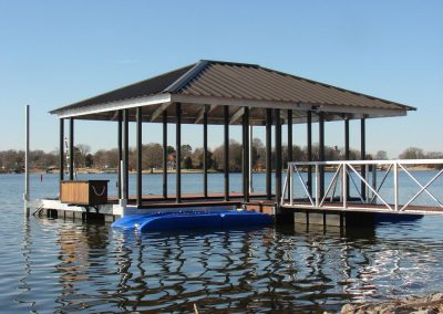 A side view of a gangway leading to an aluminum wahoo boat dock with a brown roof on a lake with trees in the background