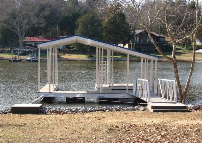 A gangway lading to an aluminum wahoo boat dock with a pitched roof on a river with houses and docks in the background