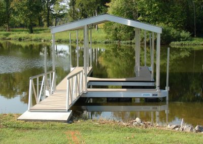 A gangway leading from a grassy shore to an aluminum wahoo dock with two boat slips and trees in the background