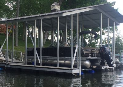 A side view of an aluminum wahoo boat dock with a pitched roof and a black pontoon boat parked on a blue boat lift