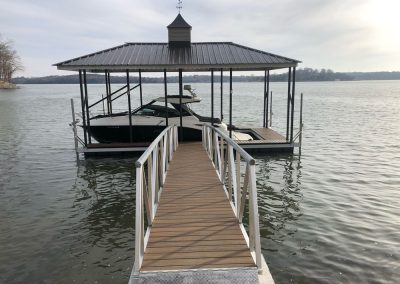Looking down a gangway to an aluminum wahoo boat dock with a dark pitched roof and a black and white boat docked under it