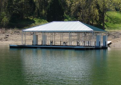 Looking across the water at a large aluminum wahoo boat dock with a silver roof and a gangway leading to shore