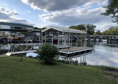 A gangway to an aluminum wahoo dock with roof on the edge of a marina with dozens of boats in the background
