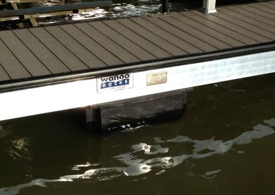 The close up of the silver side of an aluminum wahoo dock with a dark top and a wahoo dock sign on it over the water