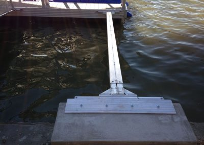 A close up of the metal fastening an aluminum wahoo boat dock to concrete on the shoreline