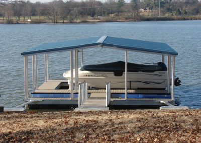 A gangway leading an aluminum wahoo boat dock with a blue roof and a white boat with a blue cover underneath it