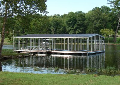 An aluminum wahoo boat dock with four boat slips and a black roof on a river with big green trees and two more docks across the way
