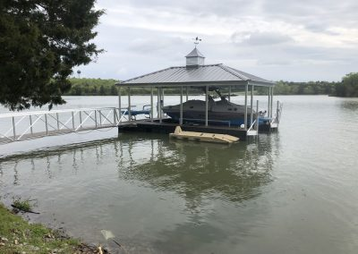 A gangway leading to an aluminum wahoo dock with a pitched roof and a boat with a cover under it and a jetski lift next to it