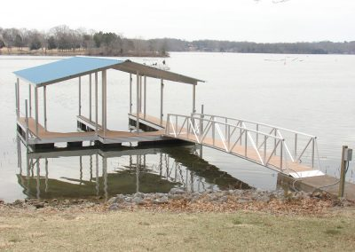 A gangway leading from a rocky shore to an aluminum wahoo dock with two boat slips and a blue roof