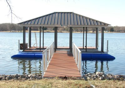 A gangway leading to an aluminum wahoo dock with a dark roof and two blue jetski lifts on either side