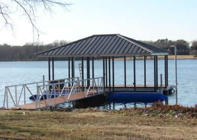 A gangway leading from a grassy shore to an aluminum wahoo dock with two blue jetski lifts