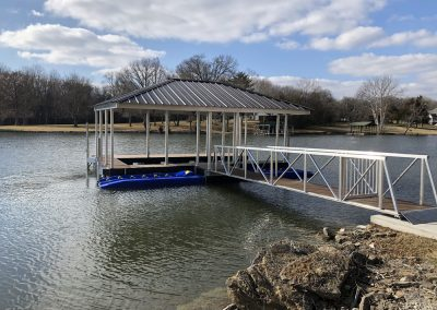 A gangway with a gate leading from a shore to an aluminum wahoo dock with a dark roof and a blue jetski lift on the side
