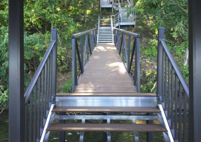 A close up of a brown gangway with black railing alternating flat and stairs leading up a tree covered hill