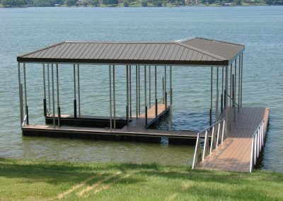 A gangway leading from a grassy shore to an aluminum wahoo dock with two slips and a brown roof with trees and houses across
