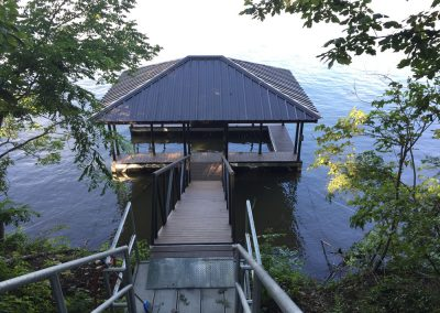 Steps leading down a tree covered hill to a gangway and an aluminum wahoo dock with a dark roof on the water