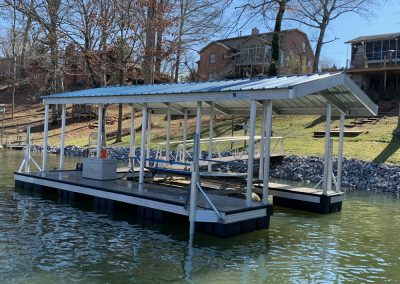 An aluminum wahoo dock on a river with a light roof and a gangway leading to a backyard with several houses in the background