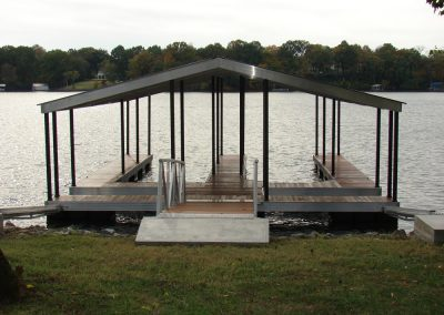 A gangway leading from a grassy shore to an aluminum wahoo dock on the river with two boat slips and a dark colored roof