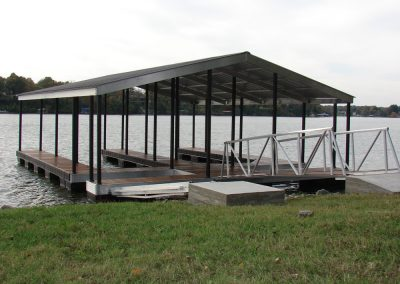 A gangway leading from a grassy shore to an aluminum wahoo deck with two boat slips and a dark roof on a river with trees in the background