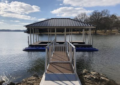 A gangway with a gate leading from a rocky shore to an aluminum wahoo dock on a river with a black roof and a blue jet-ski lift on the side