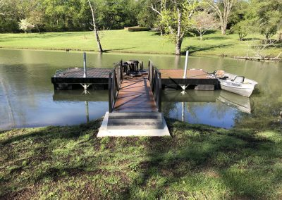 A gangway leading from a grassy bank to a rectangular aluminum wahoo dock with a small boat docked on the right side