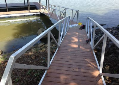 A gangway with handrails leading down a grassy bank to an aluminum wahoo dock on the water