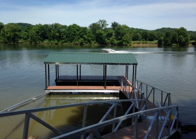 A gangway leading to an aluminum wahoo boat dock with a green roof and a boat passing on the river in the background