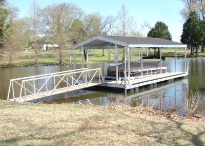 A gangway leading from a grassy bank to an aluminum wahoo dock with a tan roof and a covered pontoon boat parked under it