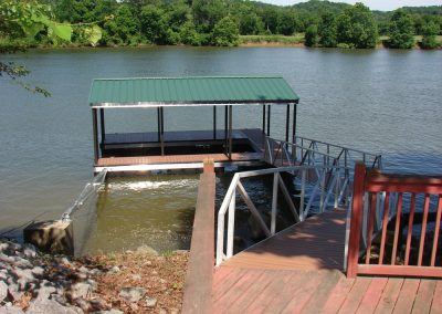 A gangway leading from a wooden deck to an aluminum wahoo dock with a green roof on the river with trees in the background