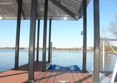 A close up of an aluminum wahoo dock and blue boat lift overlooking a lake with another dock in the background and trees across the water