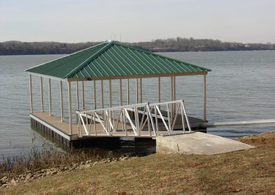 A gangway leading to an aluminum wahoo dock with a green roof on a river with trees across the way in the background