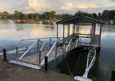 A gangway leading to an aluminum wahoo dock with a dark roof on a river with trees and boats across the way in the background