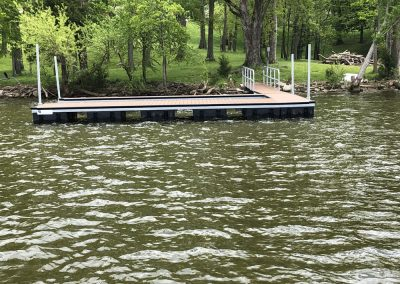 An aluminum wahoo dock on a river with a gangway leading to a grassy field with large green cypress trees