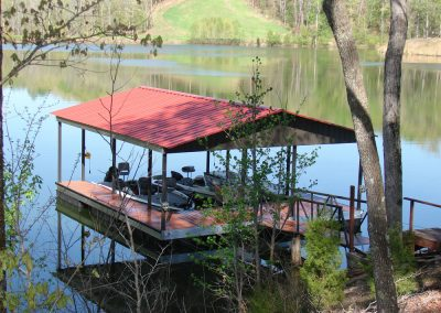 A gangway leading to an aluminum wahoo dock with a red roof on a river with two boats parked underneath it