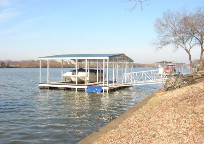 A gangway leading to an aluminum wahoo dock with a blue roof on a river with a covered boat under it and another dock in the background