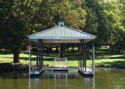 An aluminum wahoo dock with a roof and a gangway leading up to a large grassy area with big green trees