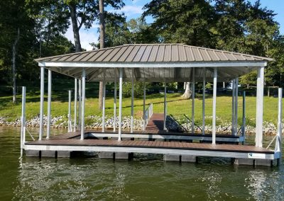 An aluminum wahoo dock with a tan roof and a gangway leading to a grassy shore with large green trees