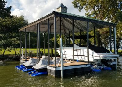 An aluminum wahoo dock with a green roof and a boat and two jet skis parked underneath it on blue lifts